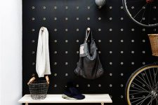 a black pegboard wall is ideal for an entryway, add shelves and hooks everywhere you want and make the space more functional