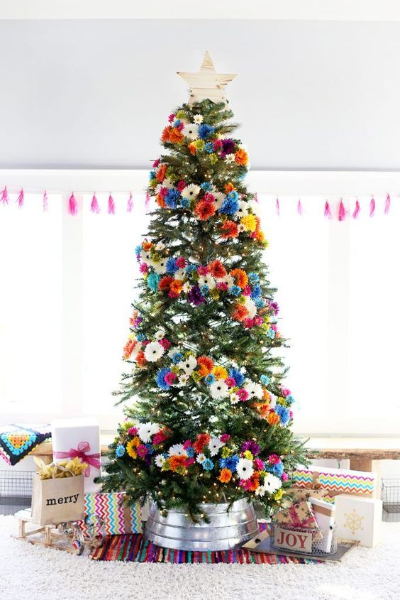 a bright Christmas tree with orange, pink, blue, white and yellow faux blooms and a wooden star topper is gorgeous