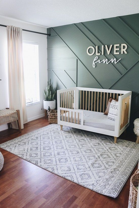 a chic contemporary nursery with a green paneled wall, mid century modern furniture, neutral textiles and potted greenery