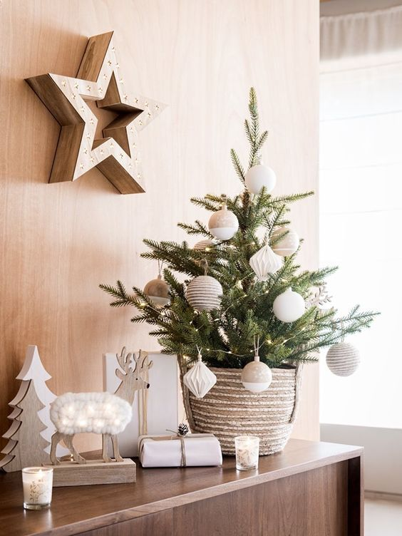 a chic tabletop Christmas tree with lights, tan and white oversized ornaments plus wooden decor around for a Nordic feel in the space