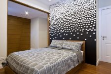 a contemporary bedroom with a black wall and a geometric 3D pattern on it for a galatic effect is wow