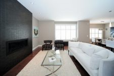 a contemporary living room with a black tile fireplace wall, a large curved sofa in white and elegant furniture around