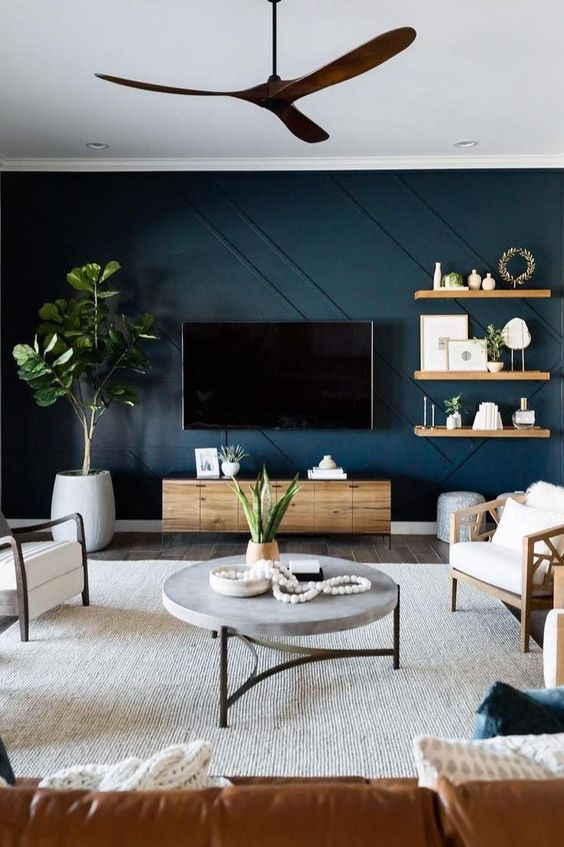a cool living room with a navy paneled accent wall, wooden furniture, a catchy round table and greenery in pots
