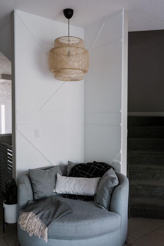 a cozy reading nook with a white geometric wall, a pendant wicker lamp and a grey round chair is very welcoming