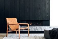 a dramatic wooden wall with a built-in fireplace and a marble slab mantel under it is a chic solution for a minimalist space