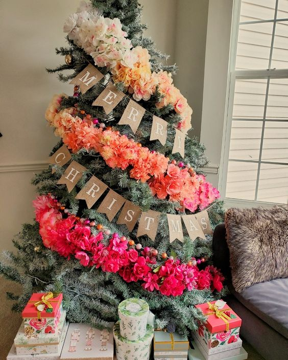 a fantastic ombre Christmas tree decorated with an ombre faux floral garland and colorful wooden beads is a lovely and bold idea