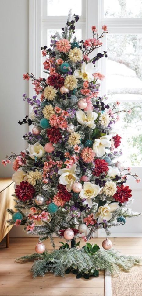 a flocked Christmas tree decorated with blooms and blooming branches, with blush ornaments and some dark foliage looks lovely