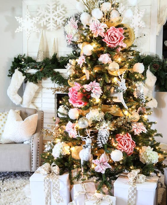 a glam Christmas tree decorated with blush and pink faux blooms, white snowballs and deer plus some lights