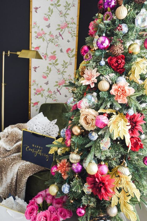 a glam Christmas tree decorated with pink, red, peachy and yellow blooms, leaves, shiny metallic and bold ornament and pinecones