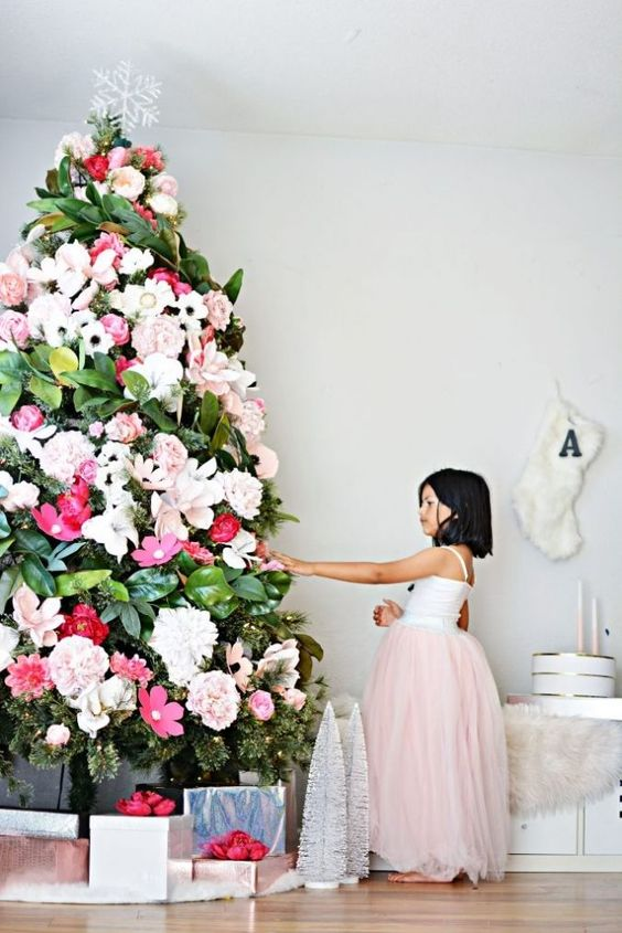 a gorgeous Christmas tree decorated with white, blush and red blooms and magnolia leaves plus a snowflake topper