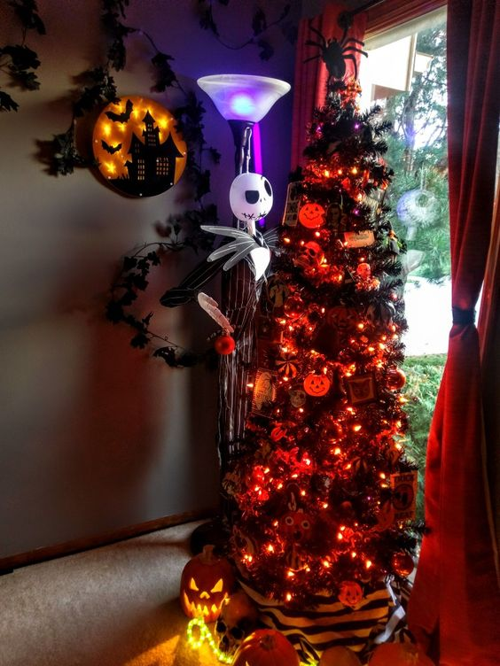 a gorgeous black Christmas tree with orange lights, pumpkins, Nightmare Before Christmas ornaments and a Jack Skellington figurine next to it