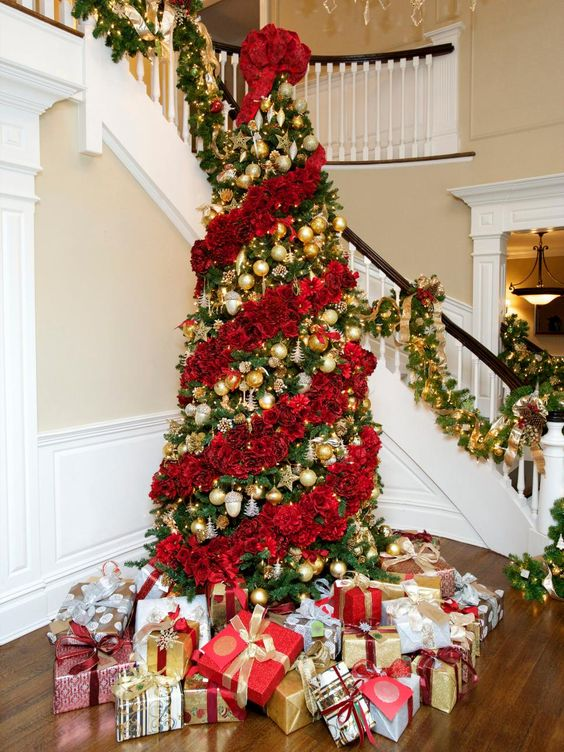 a jaw dropping Christmas tree decorated with red roses and gold ornaments in between floral garlands is magnificent