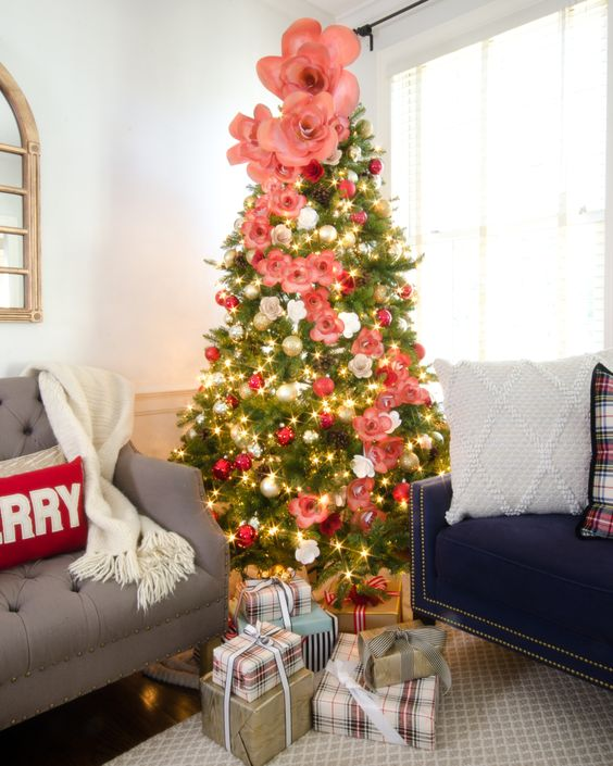 a lovely Christmas tree with silver and red ornaments, pink and white faux flowers of various sizes is beauty and chic
