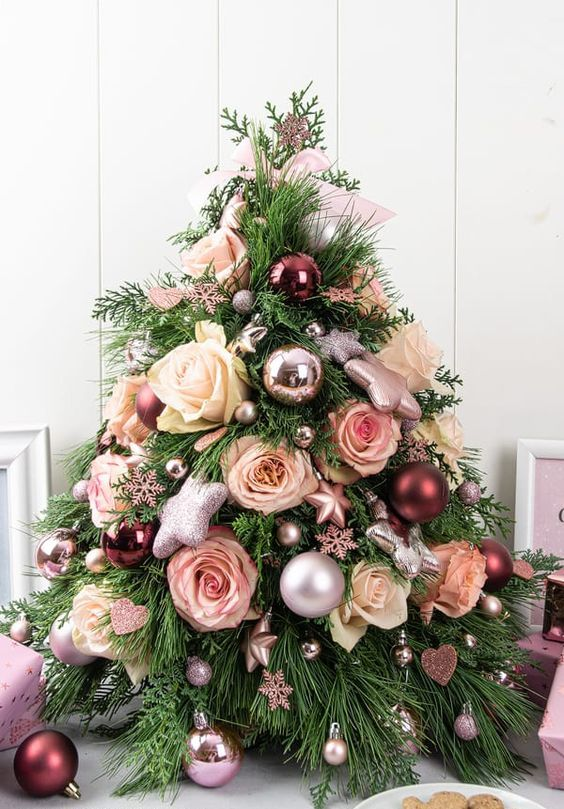 a lovely tabletop Christmas tree with blush and white roses, metallic ball and star ornaments and snowflakes is fabulous
