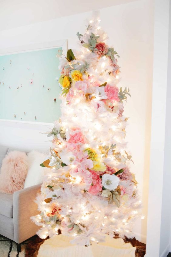 a lovely white Christmas tree with white, pink, yellow blooms, pale greenery and lights is an ethereal and chic idea to rock