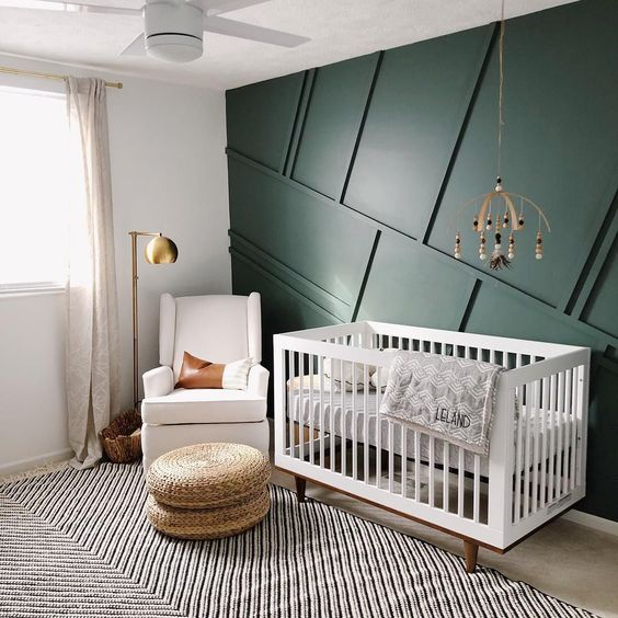 a mid century modern nursery with a green paneled wall, neutral furniture, wicker ottomans, a wooden mobile and a brass floor lamp