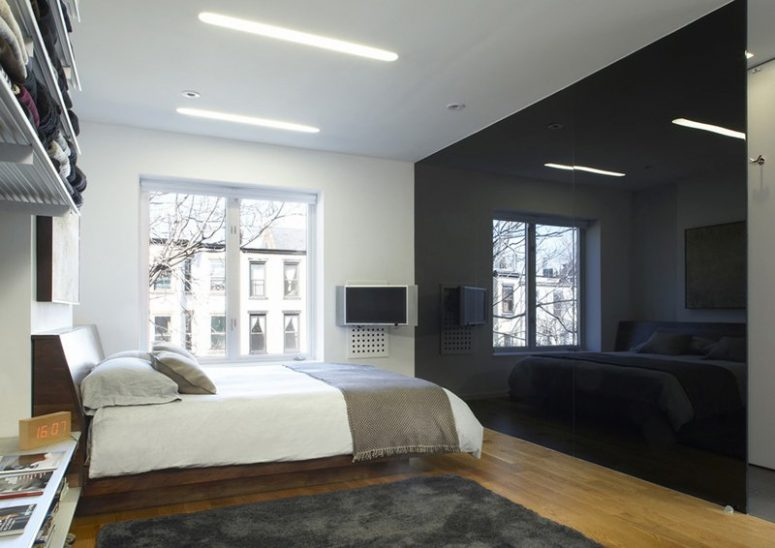 a minimalist monochromatic bedroom with a glossy black wall that brings drama and may hide a bathroom