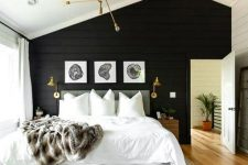 a modern farmhouse bedroom with a black wooden plank wall that makes a statement and touches of gold and brass for a shiny look