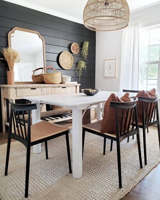 a modern farmhouse dining space with a black plank wall and black chairs that echo with it and add drama to the space