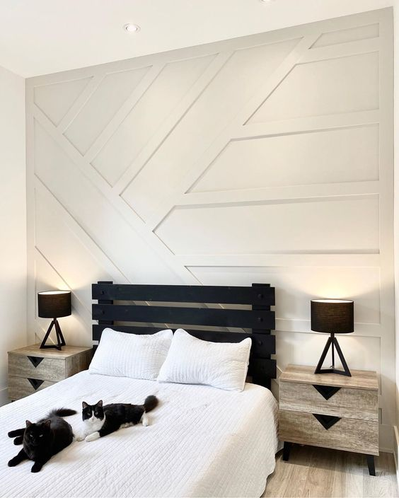 a monochromatic guest bedroom with a white paneled wall, a black bed and neutral nightstands is a chic and bold idea