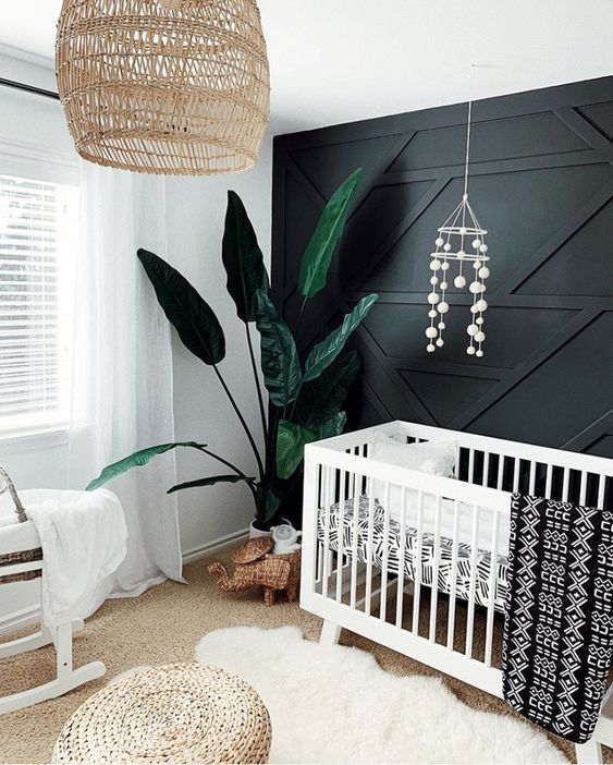 a monochromatic nursery with a black paneled wall, white furniture, a wicker pendant lamp and ottoman and a statement plant