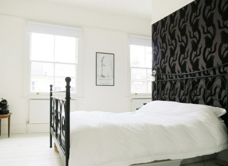 a monochromatic vintage-inspired bedroom with a black floral wallpaper wall, a black forged bed and a chic artwork