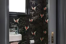 a moody and refined restroom with black fauna print wallpaper, blakc tiles on the floor and a refined gold faceted lamp