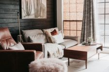 a neutral and warm-colored living room with a black plank wall, neutral furniture, pink and terracotta textiles and upholstery