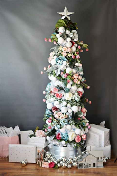 a pretty small Christmas tree decorated with white and silver ornaments, blush, pink and blue blooms and green and grey ribbons