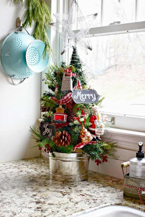 a pretty tabletop Christmas tree decorated with pinecones and mini kitchen appliances, berries in a bucket is a lovely vintage idea