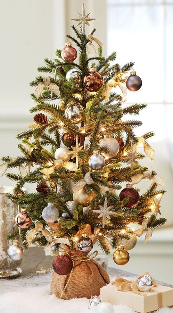a pretty tabletop Christmas tree with lights, gold and silver ornaments, pinecones and copper touches wrapped in burlap