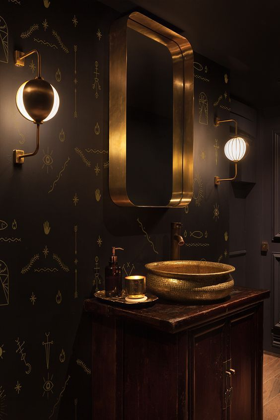 a refined bathroom with black walls and a single statement wallpaper wall with Egyptian hieroglyph prints is wow