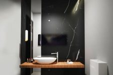 a refined black marble wall with white veins as a statement feature in a minimalist bathroom