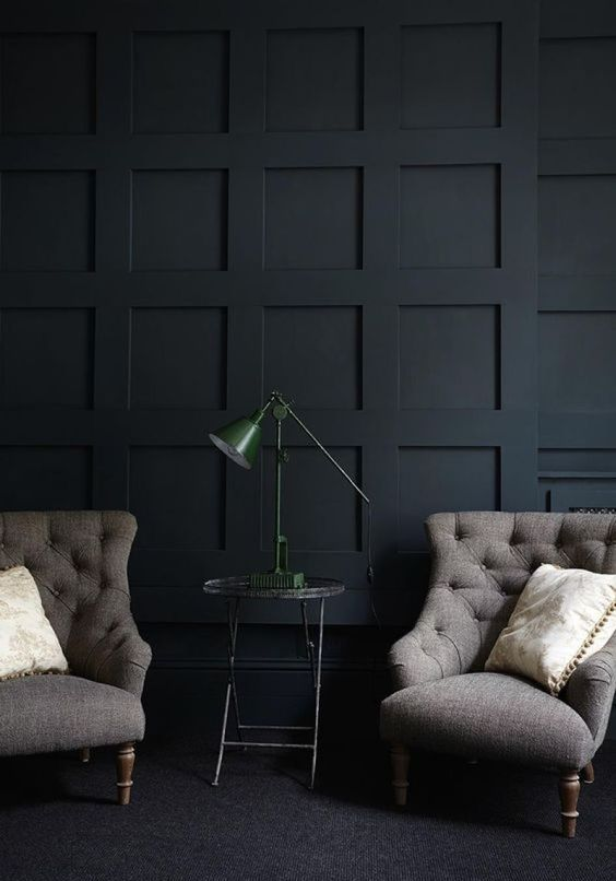 a refined black paneled wall plus vintage furniture create a chic and exquisite mood in this living room