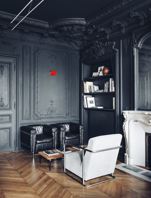 a refined living room with gorgeous black walls and a ceiling with molding and paneling, black and white furniture for a contrasting look