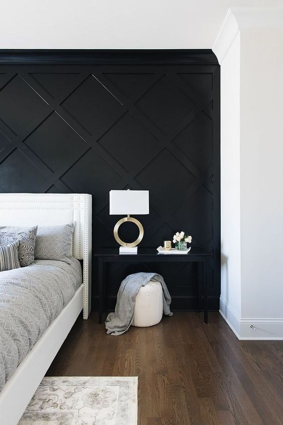 a refined monochromatic bedroom with a black geometric paneled wall, a white bed, a black nightstand, a white pouf and a chic lamp
