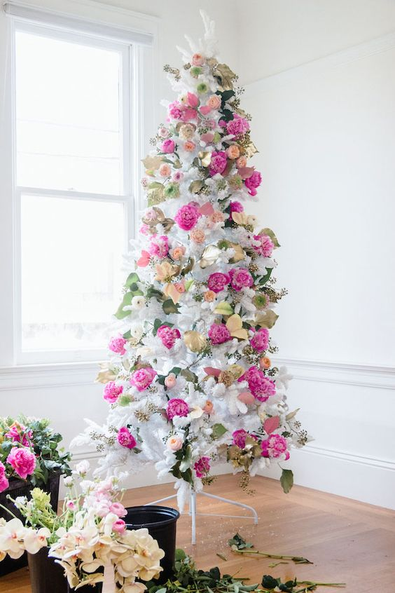a romantic white Christmas tree decorated with hot pink and blush blooms, leaves and gilded foliage is super elegant