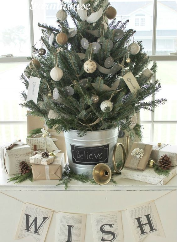 a rustic vintage tabletop Christmas tree decorated with chalkboard and twine and burlap wrapped ornaments, with vintage key prints and some pinecones around