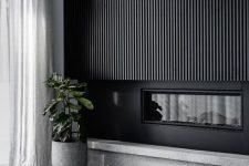 a sleek black wood slat wall with a built-in fireplace is a bold statement that will bring a dramatic touch to the space