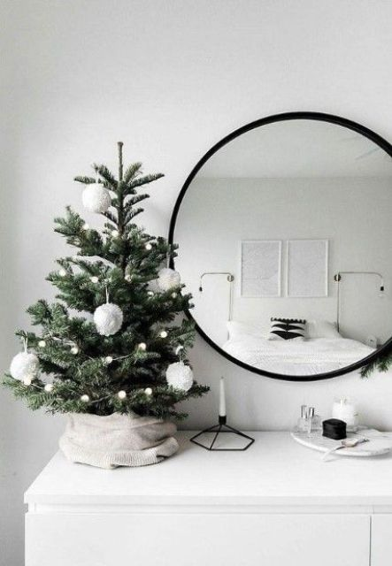 a small and simple tabletop Christmas tree with pompom garlands and large pompom ornaments for a Nordic feel