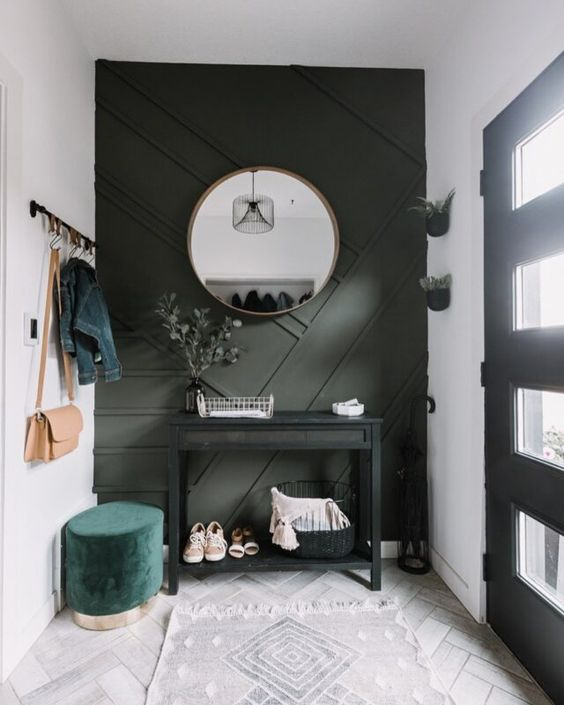 a small modern entryway with a dark green geometric wall, a black console, a green ottoman and potted greenery