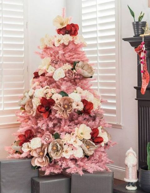 a small pink Christmas tree decorated with white, neutral, red and pink blooms   faux and natural ones for a glam feel