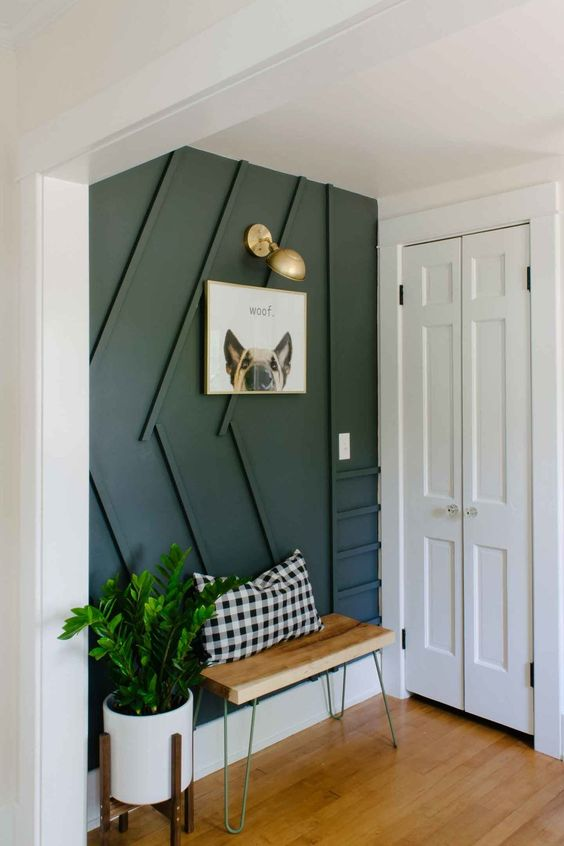 a stylish contemporary entryway with a black paneled wall, a small bench, a sconce and potted greenery is very cool