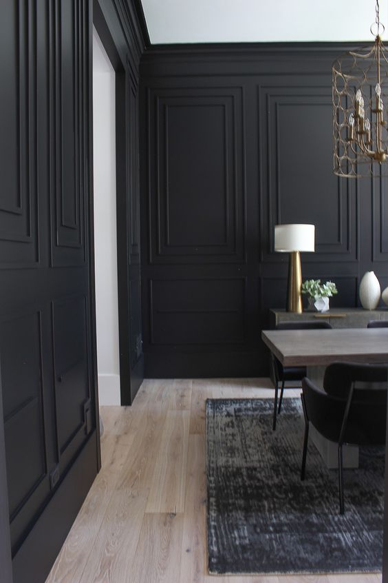 a stylish formal dining room with black paneled walls, a wooden table, a credenza and some gilded lamps