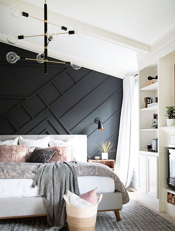 a stylish mid-century modern bedroom with a black paneled wall, an upholstered bed, built-in shelves and a stylish chandelier