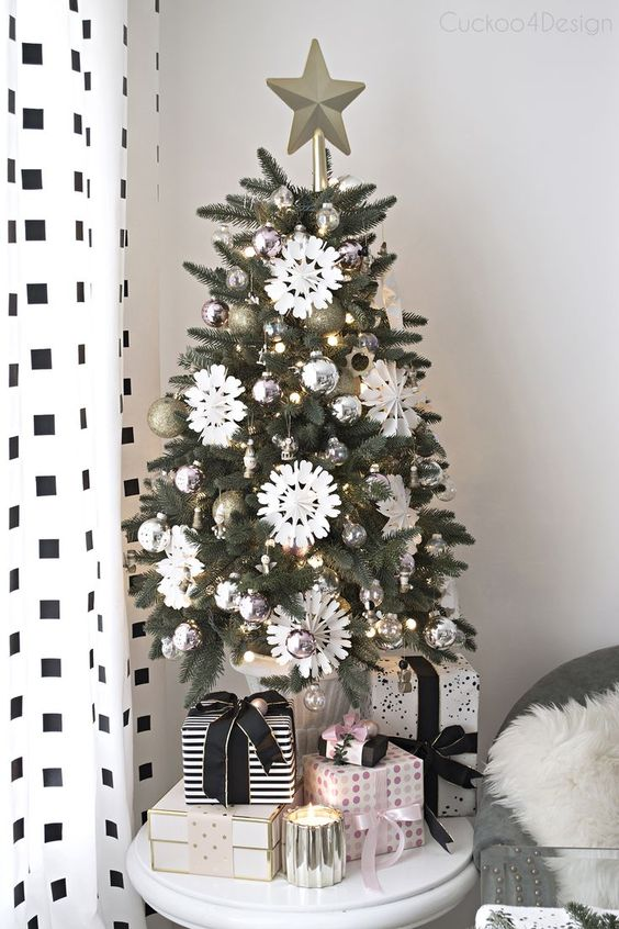 a stylish monochromatic Christmas tree with silver and gold ornaments, white snowflakes and lights plus a star topper