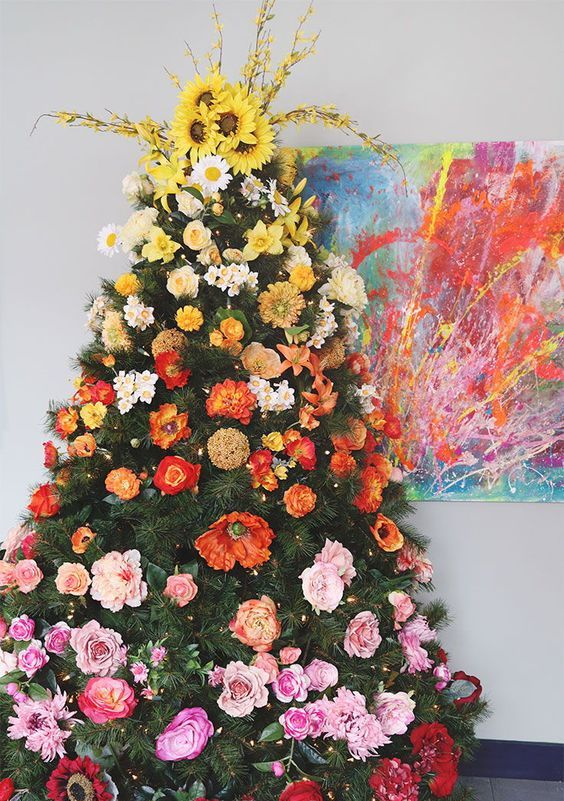 a super bold gradient Christmas tree decorated with faux blooms from yellow to deep red and with lights is beautiful