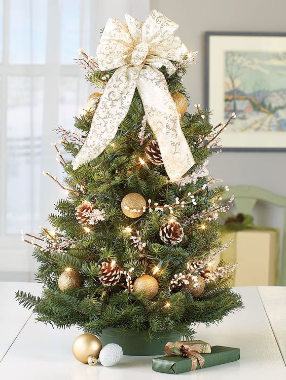 a tabletop Christmas tree decorated with lights, willow, snowy pinecones, a beautiful patterned bow on top and gold ornaments