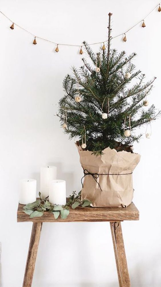 a tabletop Christmas tree decorated with wooden beads and wrapped with paper is a pretty idea with a Nordic feel