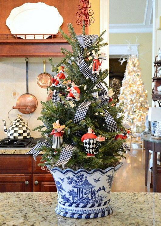 a tabletop Christmas tree in a chinoiserie planter, decorated with printed ribbons and vintage toys is a lovely and cool idea